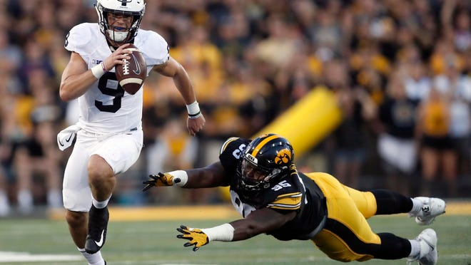 FILE - In this Sept. 23, 2017, file photo, Penn State quarterback Trace McSorley (9) runs with the ball as Iowa defensive lineman Cedrick Lattimore defends during the first half of an NCAA college football game Saturday, in Iowa City, Iowa. The 17th-ranked Nittany Lions begin the three-game gantlet of Iowa (home), Michigan (road) and Wisconsin (home) and will need to keep their offense chugging to get through it.  (AP Photo/Jeff Roberson, File)