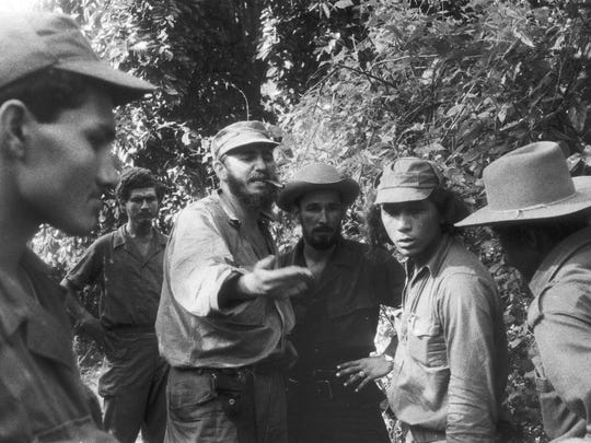 Cuban revolutionary leader Fidel Castro, cigar planted firmly in mouth, makes a point to some of his men in this 1958 photo taken by Dickey Chapelle.
