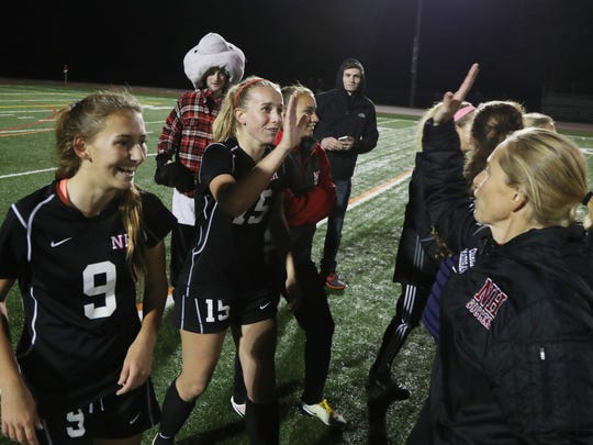 Olivia Homan and Riley Cero celebrate a win with coach Tara Madigan.