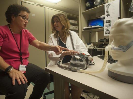 Dr. Ilene M. Rosen (right) , and clinical nurse supervisor Andrea Bergman examine a breathing mask on a mannequin at the Penn Sleep Center.