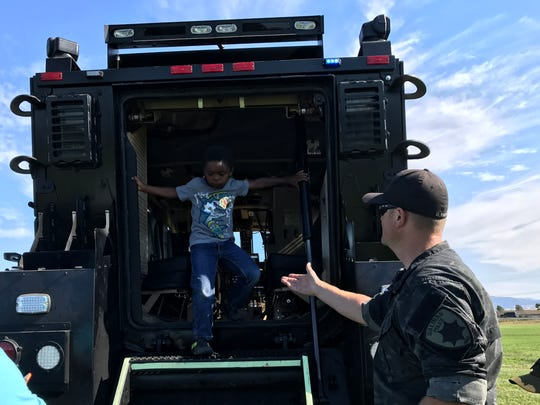 Salinas Police Officer Dale Fors offers a hand to Hector Richards, 5, as he climbs out of the Salinas Police SWAT armored rescue vehicle during National Night Out.