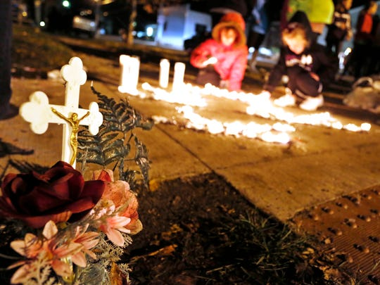 Residents gather for a candlelight vigil Tuesday, November