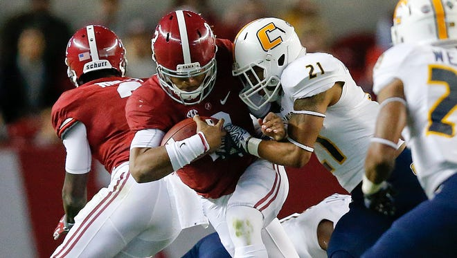 Alabama quarterback Jalen Hurts, runs the ball against Chattanooga defensive back Montrell Pardue, during the first half of an NCAA college football game, Saturday, Nov. 19, 2016, in Tuscaloosa, Ala.