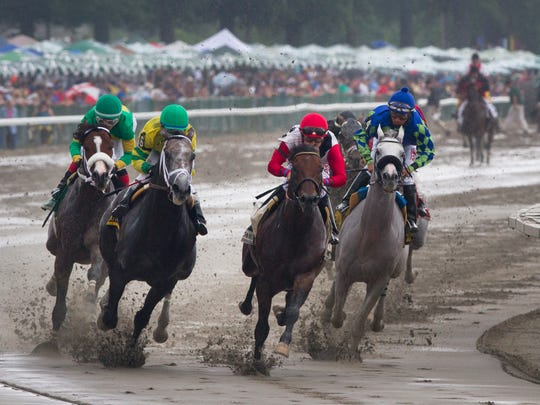 Joe Bravo (in red-center) leads the field around the turn on Bradester en route to their win in the Grade II Monmouth Cup on Haskell Day at Monmouth Park.