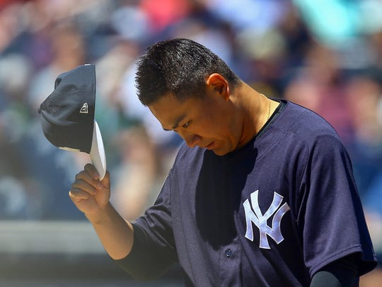 New York Yankees starting pitcher Masahiro Tanaka (19) tips his hat as he walks off the field during the fourth inning of a Spring Training baseball game against the Boston Red Sox at George M. Steinbrenner Field.