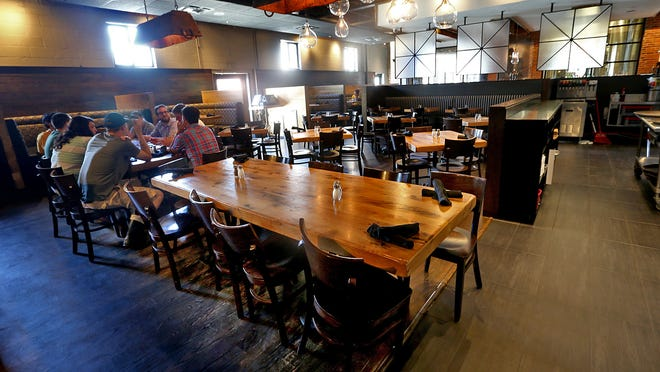 A group of friends enjoy a meal earlier this month in the dining area at Exile Brewery Co.