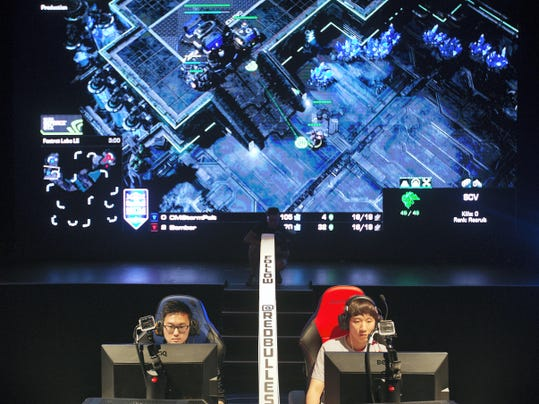 """FILE - In this July 13, 2014 file photo, Choi Seong Hun, left, who goes by the gaming name """"PoLt"""" and Choi Ji Sung, known as """"Bomber,"""" both of South Korea, are separated by a divider as they compete against each other in the finals of the Red Bull Battle Grounds """"StarCraft II"""" video game tournament in Atlanta. The next ally in competitive gaming's fight for mainstream awareness might be marketers. At an invite-only gathering of marketing executives Wednesday, May 6, 2015, representatives from companies like State Farm and McDonald's were looking to esports to potentially capture new consumers. (AP Photo/David Goldman, File)"""