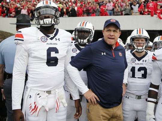 Auburn coach Gus Malzahn get set to take the field between quarterbacks Jeremy Johnson (6) and Sean White (13).