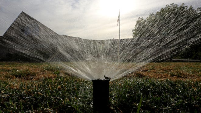 Sprinklers water a lawn in Sacramento, Calif., on July 15, 2014.