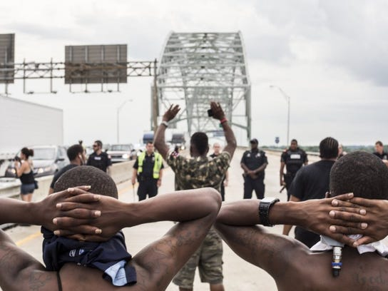 Black Lives Matter supporters hold their hands behind their heads while facing a line of police officers on the Interstate 40 bridge over the Mississippi River on July 10, 2016. Traffic was at a standstill on both sides of the bridge that evening as the estimated crowd on the bridge swelled to more than 1,000.
