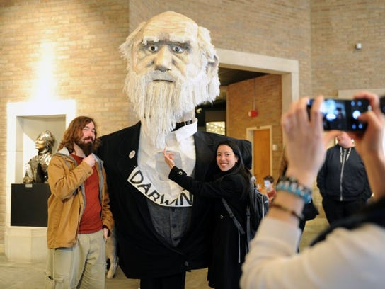 University of Tennessee graduate students Orlando Schwery and Angela Chuang pose for a photo with biologist Charles Darwin at his 207th birthday party in the McClung Museum of Natural History and Culture at the University of Tennessee.