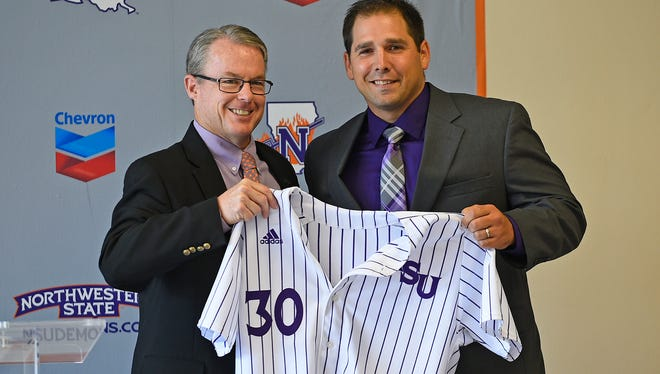 New Northwestern State coach Bobby Barbier (right) shows off his jersey with athletics director Greg Burke.