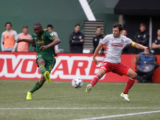 Portland's Fanendo Adi, left, fires a shot on goal as the Portland Timbers hosted Atlanta United FC in a MLS match at in Portland, Ore., Sunday, May 14, 2017.  (Sean Meagher/The Oregonian via AP)
