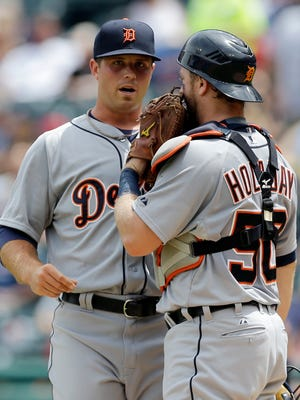 Buck Farmer talks with catcher Bryan Holaday in the first inning Wednesday.