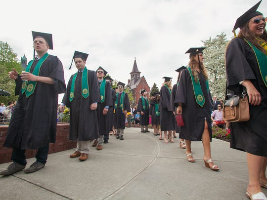 Graduates walk in a procession line at the University of Vermont's commencement Sunday.