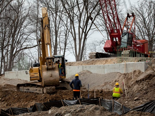 Workers rebuild the Gratiot Road bridge over the Pine