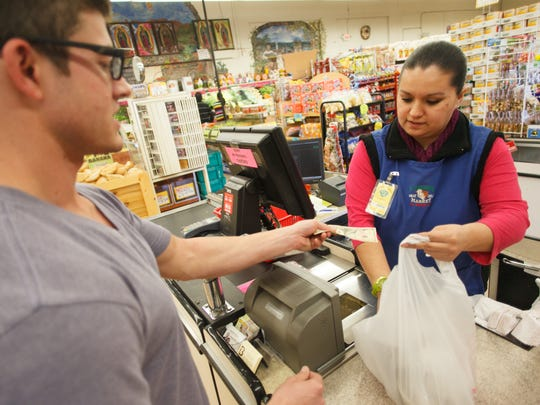 Yessica Puertas, a cashier at 3 Amigos grocery store in St. George, rings up a purchase for customer Trevor Floreani at the local grocer Monday, Jan. 27, 2014. The cost of living in Southern Utah has dropped to 91.6% of the national average according to the Business Resource Center at Dixie State University.