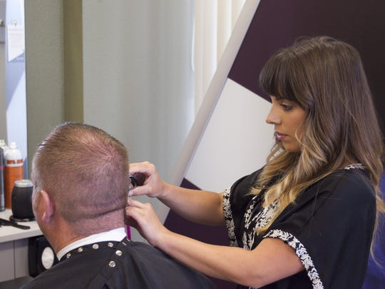 Lauren Ludlow, a hair stylist at Great Clips, cuts her client's hair on Tuesday July 29, 2014.
