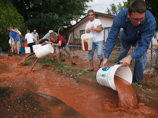 Volunteers use buckets to remove water from the front yard of a home that was flooded in Washington City after heavy rains sent a river of muddy water through the center of town in late August. The area was back under a flash flood watch Sunday with moisture from Tropical Storm Norbert expected to bring heavy rains Monday and Tuesday.