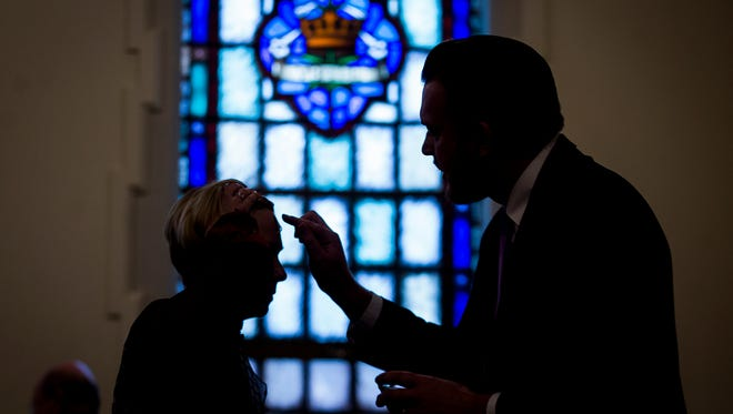 Pastor Stacee Fischer Gehring (left) receives ashes from Rob Frey, principal of St. Lawrence Catholic School, during an Ash Wednesday service at High Street United Methodist Church Tuesday.