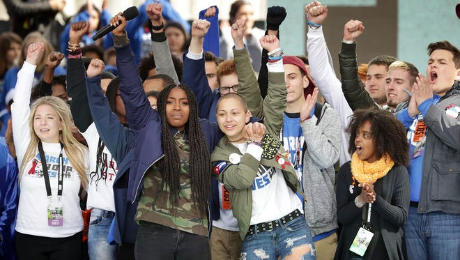 Students from Marjory Stoneman Douglas High School, including Emma Gonzalez, center, stand together with other young victims of gun violence at the conclusion of the March for Our Lives rally March 24 in Washington, D.C.