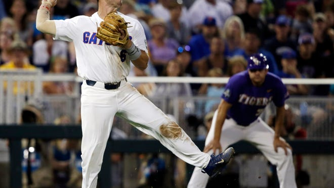 File- This June 27, 2017,  file photo  shows Florida third baseman Jonathan India (6) holding onto the ball allowing LSU's Zach Watson a base hit during the seventh inning in Game 2 of the NCAA College World Series baseball finals in Omaha, Neb.  India has been an offensive force for the defending College World Series champions, hitting .364 with 18 homers and 45 RBIs through Saturday's NCAA Tournament regional games. He's the 12th player in school history to post 20 or more homers, 100 or more RBIs and 30 or more stolen bases in his career. India is one of the best all-around hitters in this year's draft class, as evidenced by his 24-game hitting streak earlier this season. (AP Photo/Nati Harnik, File)