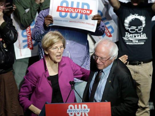 Sens. Elizabeth Warren, D-Mass., left, and Bernie Sanders,