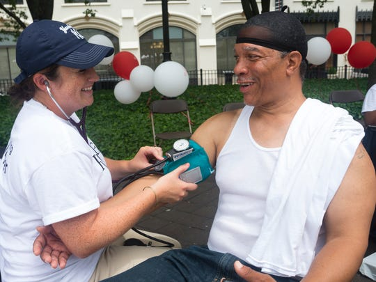 Second-year Rutgers School of Health Professions physician assistant student Megan Wheatley checks Tracy Reed's blood pressure during health screenings at the Newark Downtown District Farmers Market at PSE&G Plaza on July 14.