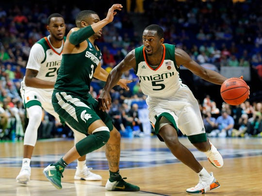 FILE - In this March 17, 2017, file photo, Michigan State guard Alvin Ellis III (3) defends as Miami guard Davon Reed (5) moves to the basket in the first half of a first-round game in the men's NCAA college basketball tournament in Tulsa, Okla. Reed has crisscrossed the country almost nonstop for the last few weeks, playing anywhere he could with hopes of raising his NBA draft stock. (AP Photo/Tony Gutierrez, File)