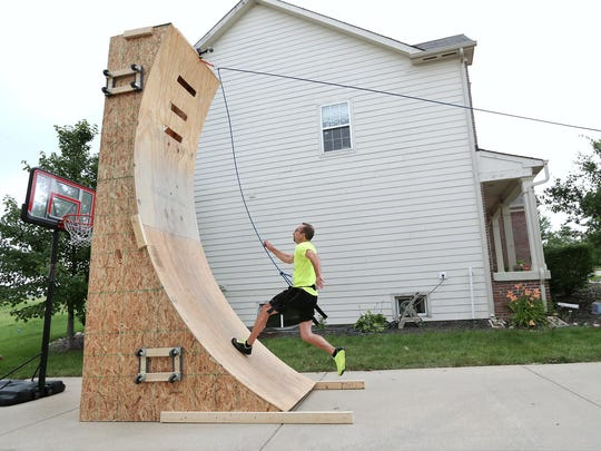 "Fishers High School teacher Andrew Smith, 45, sprints up a wooden wall as he practices for ""American Ninja Warrior."""