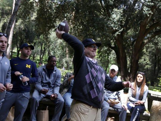 Michigan football coach Jim Harbaugh throws a football