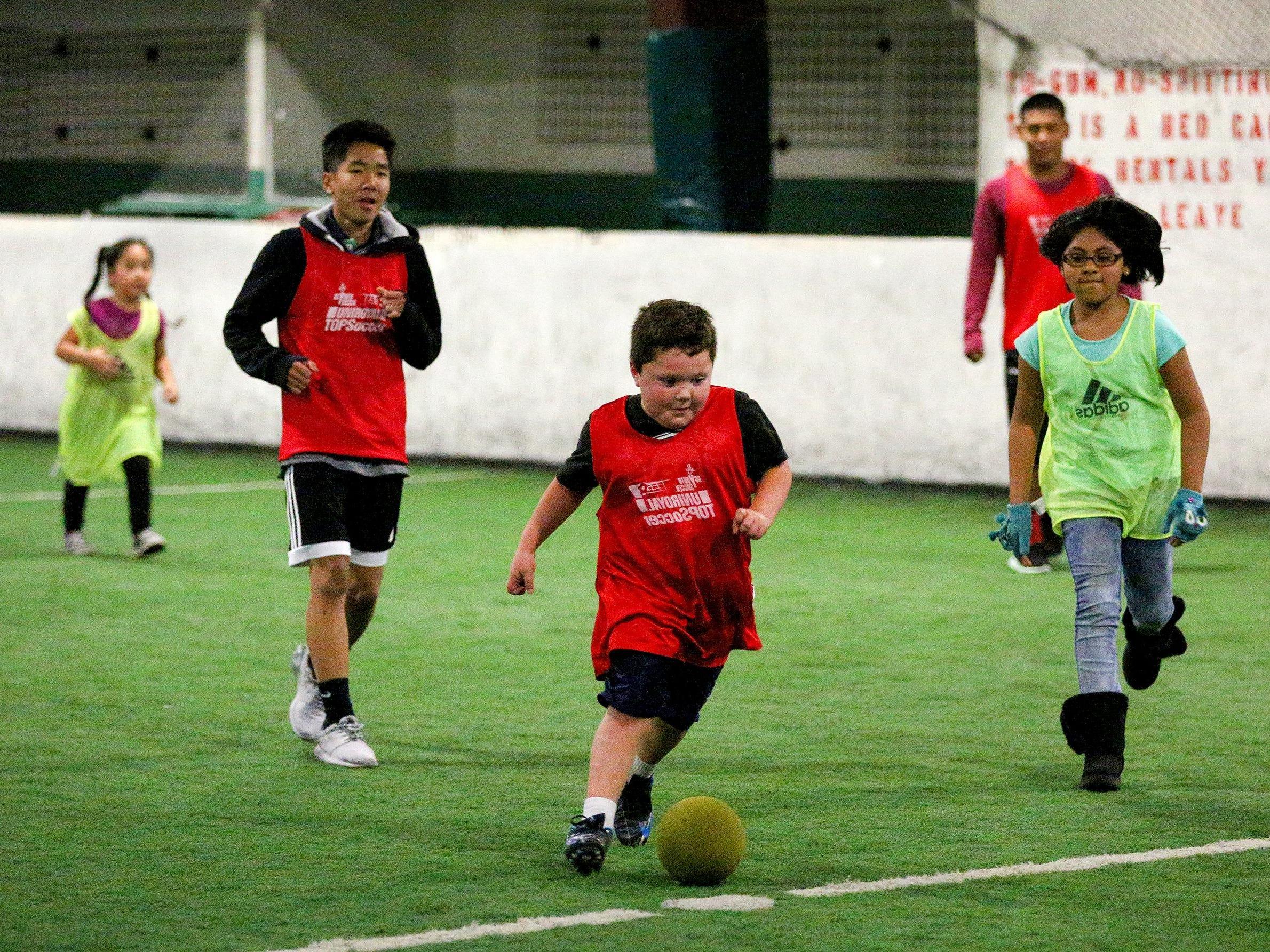 Jaiden Hernandez, 7, dribbles the ball during a youth soccer program with North Salem High School's boys soccer team, Wednesday, November 18, 2015, at Salem Indoor Soccer Center in Salem, Ore.