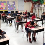 In this April 14, 2015 photograph, third grade students in Stephanie Slayter's class at Cherokee Elementary School in Pascagoula, Mississippi, wait for teachers to pick up computers after completing a computerized 50-question multiple choice third-grade reading test. Across Mississippi, 38,000 third graders, their parents and teachers are waiting to find out whether they'll be moving on to fourth grade.