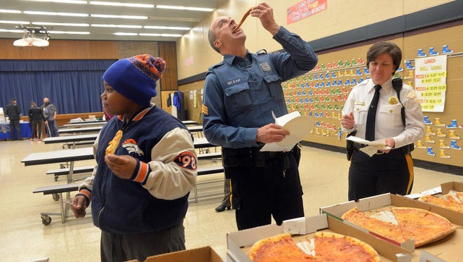 """Sixth grader Raymond Thomas, 11, eats pizza along with Vineland police Sgt. Daniel Fay and Lt. Lene Bowers (from left) during the """"Talk to Your Kids About Drugs Over Dinner"""" event at Rossi Intermediate School in Vineland, Feb. 9."""