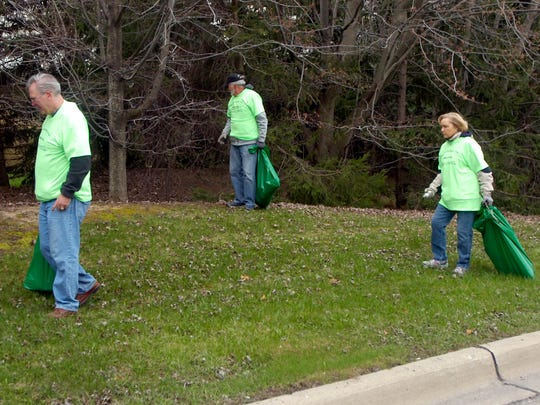 Norm Nicholson and Pat and Marlene Strang were among the volunteers picking up trash on Litter Clean-Up Day in the Old Homestead subdivision.