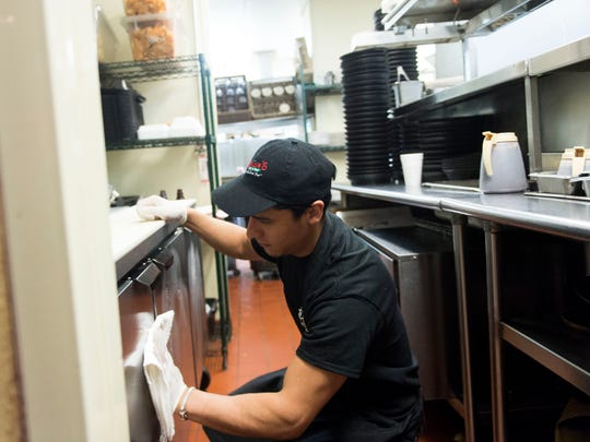 Allan Rivera cleans his station at Blaine's Grill and Bar in Gatlinburg. Rivera works as an expediter and coordinates food orders between the kitchen and dining room.