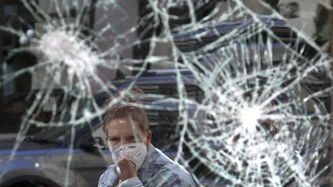 A woman looks at a smashed storefront window in Boston's Downtown Crossing on Monday, June 1. The destruction caused by vandals and looters in cities across the country,  who struck as demonstrators took to the streets in reaction to the killing of George Floyd in Minneapolis, has devastated small businesses already reeling from the coronavirus outbreak.