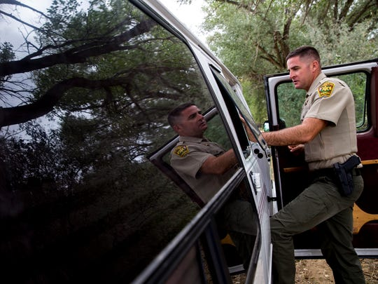 San Juan County Deputy Mike Rietz, a sex offender registration and tracking unit member,  speaks with a registered sex offender Thursday in Aztec.