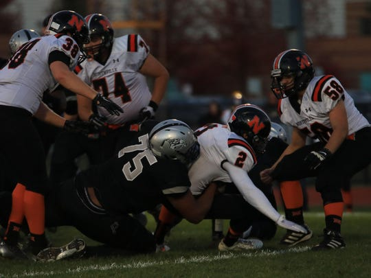 Plymouth senior Michael Jordan (middle) sacks Northville quarterback Justin Zimbo during the conference title game. On Saturday, he announced he will leave high school early and enroll in January at Ohio State University.