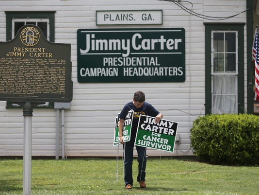 People place signs in support of Former US President Jimmy Carter