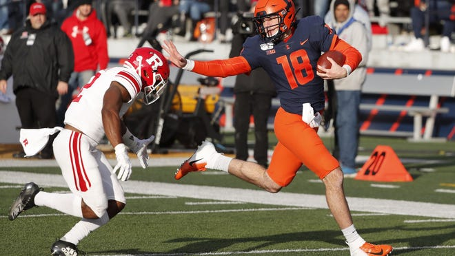 Illinois quarterback Brandon Peters runs for 54-yards as Rutgers defensive back Christian Izien chases during the second half of an NCAA college football game Saturday, Nov. 2, 2019, in Champaign, Ill.