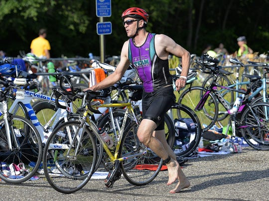 A participant in the Graniteman Triathlon Clearwater transitions from the swimming portion of the race to the biking portion Saturday at Warner Lake County Park.