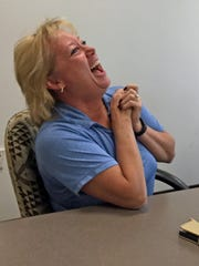 "Tracey Bramble, left, laughs in the middle of an Iowa Department of Transportation ""Message Monday"" meeting with Steve Gent, director of traffic safetey."