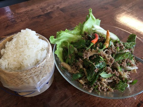 Beef laab with thinly sliced beef, tripe, scallions, cilantro, mint, chili peppers and lime juice is served with sticky rice. Cost is $15 at Sticky Rice Cafe .