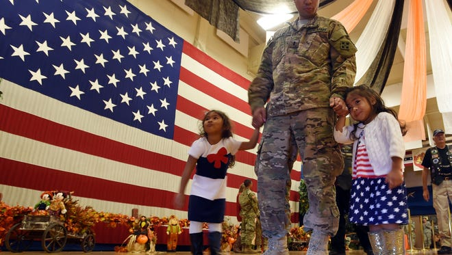 Lt. Daniel Oglesby leaves hand in hand with his daughters, Layla Oglesby and Karas Oglesby, right to left, after a homecoming at Ft. Carson, Colo., that welcomed home the 3rd Armored BCT, 4th I.D. on Tuesday, Oct. 6, 2015. (Jerilee Bennett/The Gazette via AP)