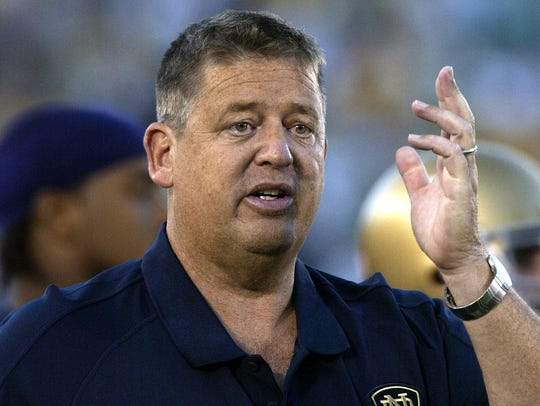 Notre Dame coach Charlie Weis motions to a player during