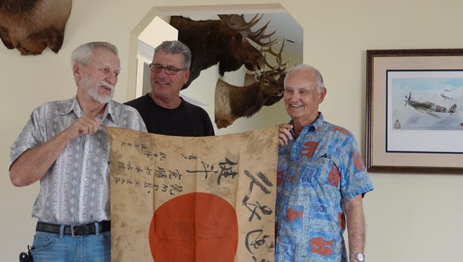 Pete Barillier, left, Robert Wagner and Tom Hodges pose with a Japanese soldier's flag from World War II at Wagner's home in the Santa Rosa Valley. Hodges hopes the flag can be returned to the soldier's family in Japan.