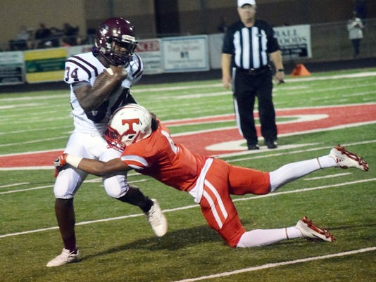 Tioga's Tyd'arian Quinney (4, right) wraps up Grant's Deante Lacour (left).