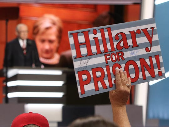 "Florida delegate Henry Allen holds a 'Prison for Hillary"" sign on the floor of the Quicken Loans Arena in Cleveland, OH, on the second day of the Republican National Convention Tuesday July 19, 2016.  Former US Attorney General Michael Mukasey is speaking in the background."