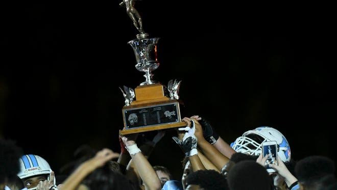 Rockledge High football players hold high the Barbecue Bowl trophy after beating Cocoa in 2017.